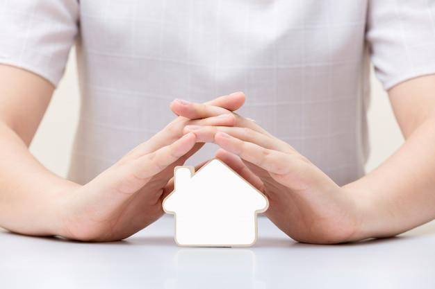 Haus mit weißem leerzeichen unter den händen der frau. versicherungs- und hausschutzkonzept. Premium Fotos