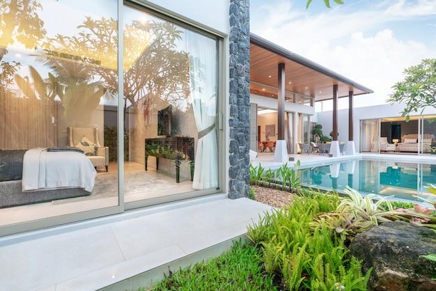 Haus oder haus außendesign mit tropischer poolvilla mit grünem garten und schlafzimmer Premium Fotos