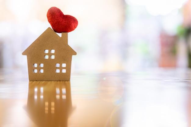 Haus und herz modellieren auf hölzerner tabelle, ein symbol für bau Premium Fotos