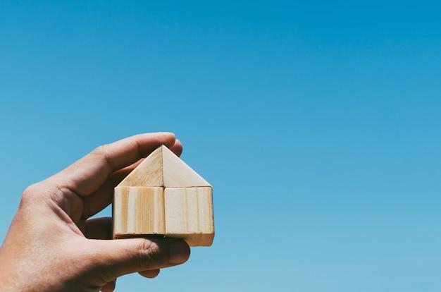 Haus vom holzblock in der menschlichen hand mit blauem himmel Premium Fotos