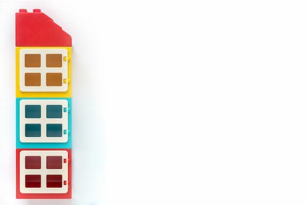 Haus von plastikerbauerziegelsteinen auf weißem hintergrund. beliebtes spielzeug. freier platz für text Premium Fotos