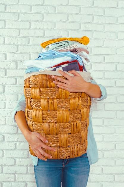 Hausfrau bringt einen riesigen haufen wäsche auf das bügelbrett Premium Fotos