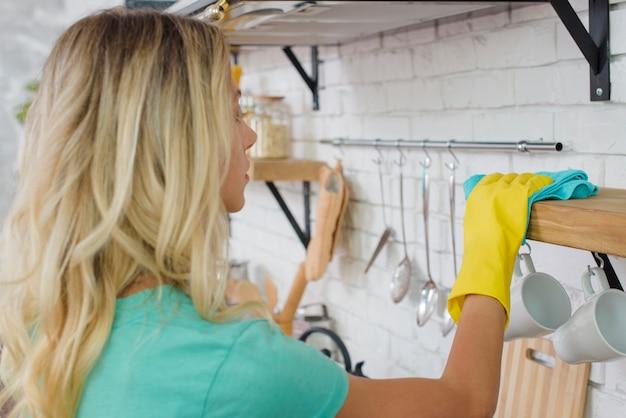 Hausfrau mit gummihandschuhen, die regal mit mikrofasertuch abwischen Kostenlose Fotos