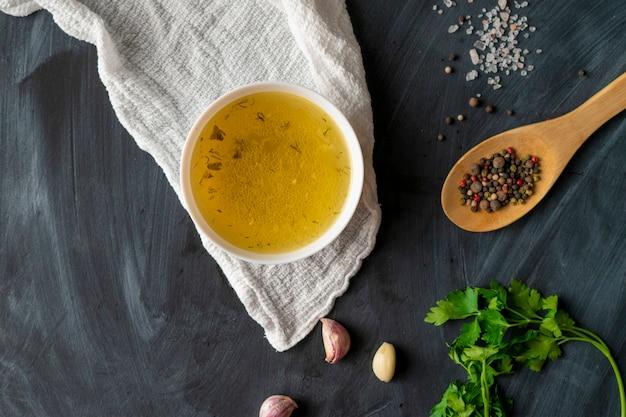 Hausgemachte boullion oder klare suppe in einer keramikschale in der küche, gesunde ernährung und diäten Premium Fotos