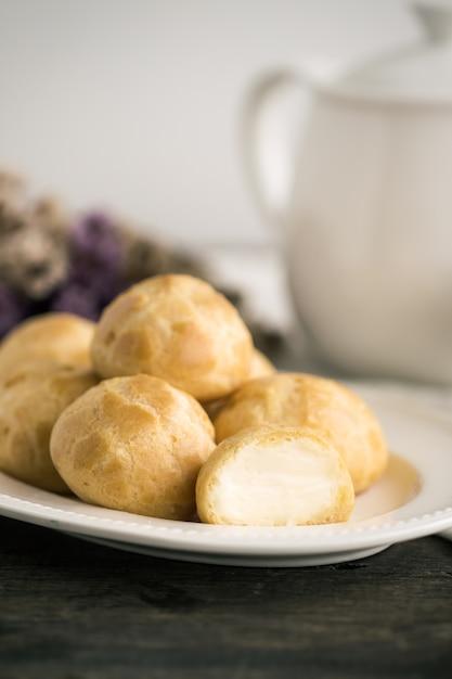 Hausgemachte cream puffs oder choux cream oder eclairs servieren mit tee in weißen topf oder tasse kaffee Premium Fotos