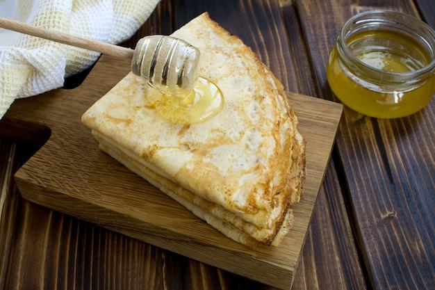 Hausgemachte crepes mit honig auf dem holzschneidebrett Premium Fotos