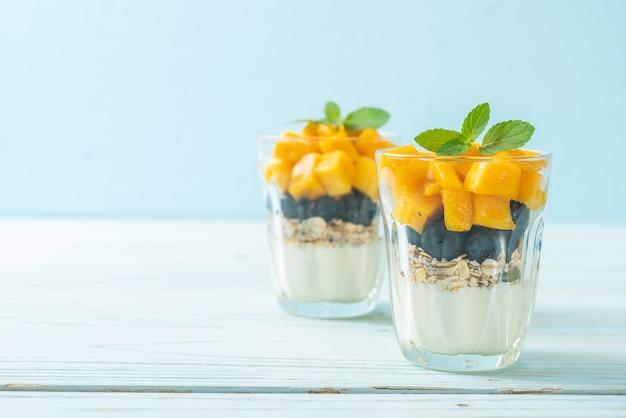 Hausgemachte frische mango und frische blaubeere mit joghurt und müsli. gesunde ernährung Premium Fotos