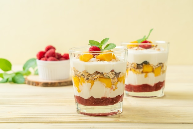 Hausgemachte frische mango und frische himbeere mit joghurt und müsli - gesunde ernährung Premium Fotos