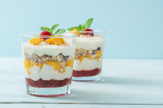 Hausgemachte frische mango und frische himbeere mit joghurt und müsli. gesunde ernährung Premium Fotos
