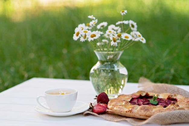 Hausgemachte galette erdbeerkuchen, eine tasse tee und eine vase mit einem blumenstrauß aus gänseblümchen. Premium Fotos