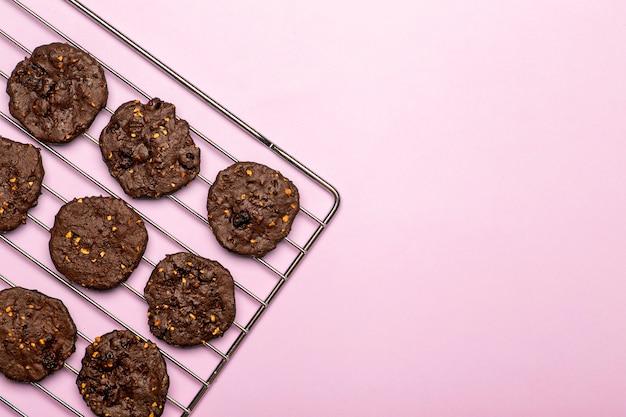 Hausgemachte glutenfreie schokoladenkekse mit müsli, nüssen und bio-kakao. plätzchen und gebäck vom roggenmehl auf einem farbigen hintergrund. glutenfreies konzept Premium Fotos