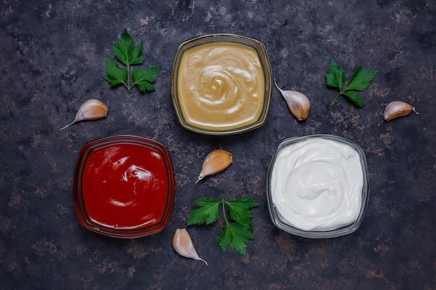 Hausgemachte ketchup, senf und mayonnaise sauce und zutaten auf dunkel. ansicht von oben Kostenlose Fotos