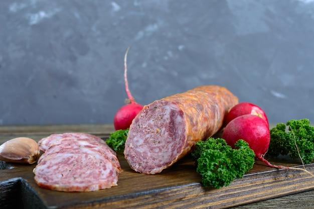 Hausgemachte kraftwurstsalami, in scheiben geschnitten auf einem holzbrett. Premium Fotos