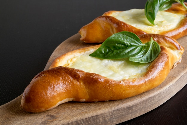 Hausgemachte kuchen, khachapuri mit käse und basilikum. Premium Fotos
