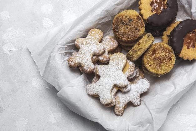 Hausgemachte lebkuchen-, zimt- und schokoladenplätzchen auf weißem raum von oben. flach liegen Premium Fotos