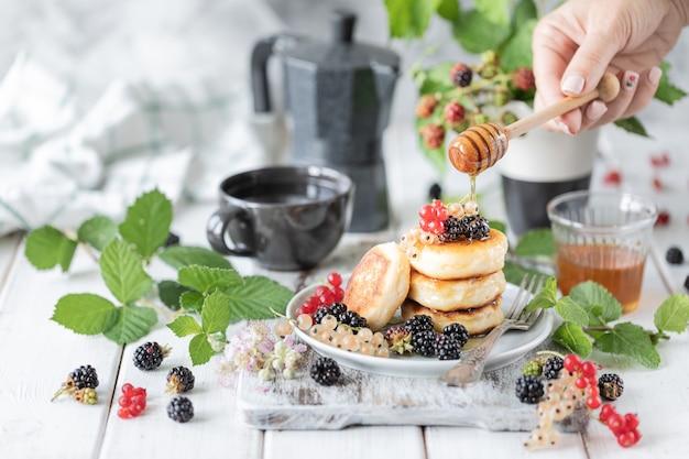 Hausgemachte pfannkuchen mit beeren und wecker auf weißem holz Premium Fotos
