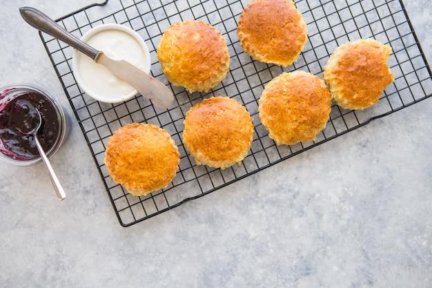 Hausgemachte rosinen-scones werden mit hausgemachter erdbeermarmelade, clotted cream und tee serviert Premium Fotos