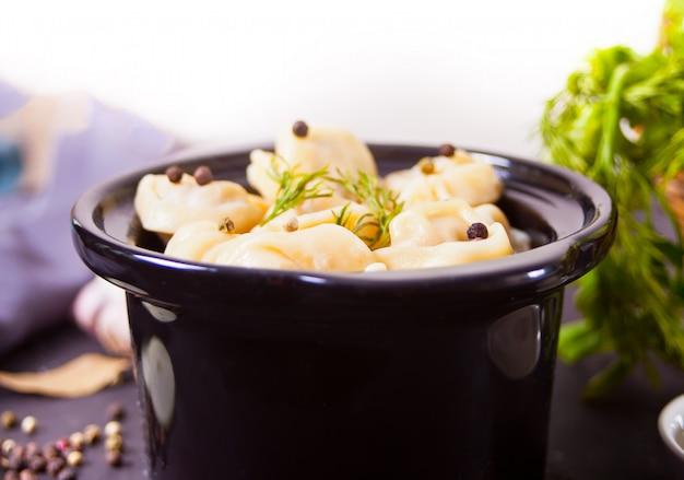 Hausgemachte russische pelmeni fleischknödel italienische ravioli in der kleinen schwarzen pfanne. Premium Fotos