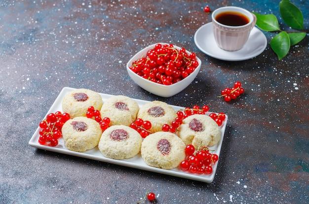 Hausgemachte rustikale marmelade der roten johannisbeere, die kekse mit kokosnuss und tasse tee füllt Kostenlose Fotos