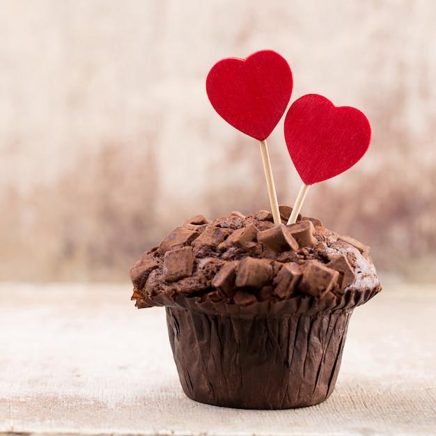 Hausgemachte schokoladenmuffins mit herz, weinlesehintergrund. Premium Fotos