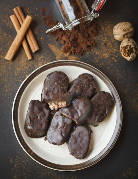 Hausgemachte schokoriegel mit walnüssen, kakao und zimt in einem weißen teller auf einer schwarzen oberfläche Kostenlose Fotos