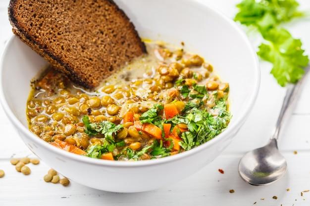 Hausgemachte vegane linsensuppe mit gemüse, brot und koriander Premium Fotos