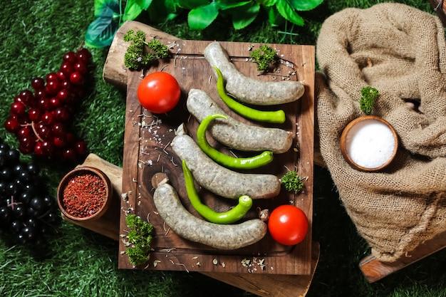Hausgemachte würste auf dem holzbrett pfeffer tomatengrün salz Kostenlose Fotos