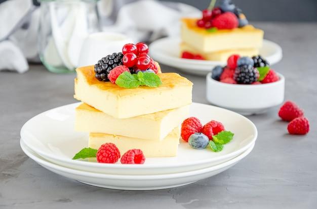 Hausgemachter hüttenkäse-auflauf mit frischen beeren und minze auf einem weißen teller. gesundes frühstück. horizontaler kopierbereich. Premium Fotos