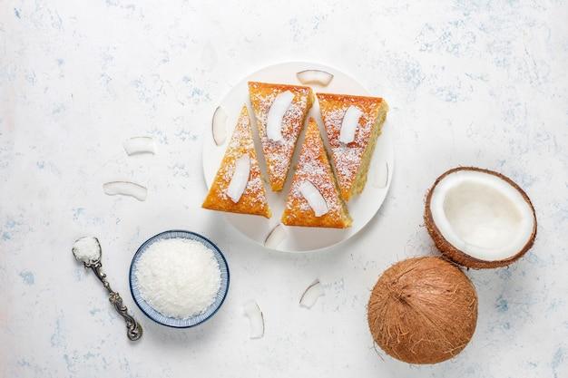 Hausgemachter köstlicher kokosnusskuchen mit halber kokosnuss Kostenlose Fotos