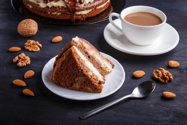 Hausgemachter schokoladenkuchen mit milchcreme, karamell und mandeln. tasse kaffee. Premium Fotos