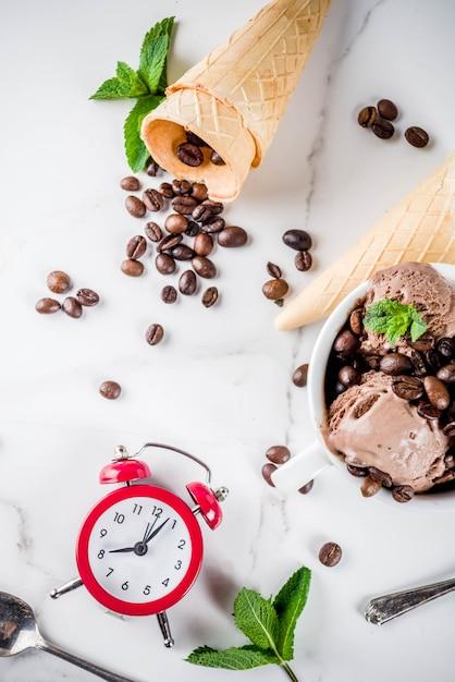 Hausgemachtes kaffeeeis, serviert mit kaffeebohnen und minze, mit eistüten und löffeln auf dem bild. weißer marmor hintergrund, Premium Fotos