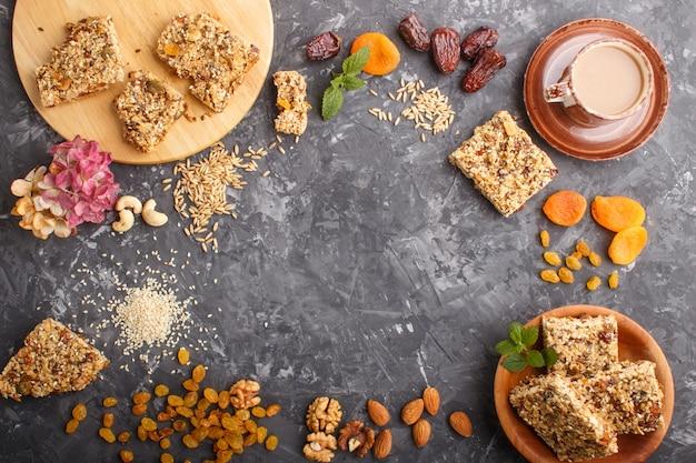 Hausgemachtes müsli aus haferflocken, datteln, getrockneten aprikosen, rosinen, nüssen mit einer tasse kaffee. draufsicht, rahmenhintergrund Premium Fotos