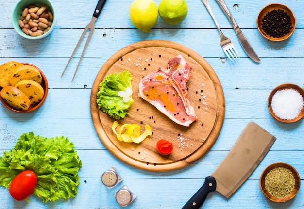 Hausgemachtes schweinefleischsteak mit gewürzen, blattsalat auf holzbrett und teller, Premium Fotos