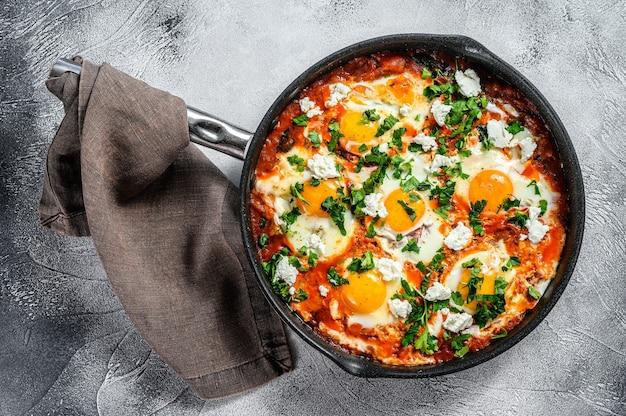 Hausgemachtes shakshuka, spiegeleier, zwiebel, paprika, tomaten und petersilie in einer pfanne. grauer hintergrund. draufsicht. Premium Fotos