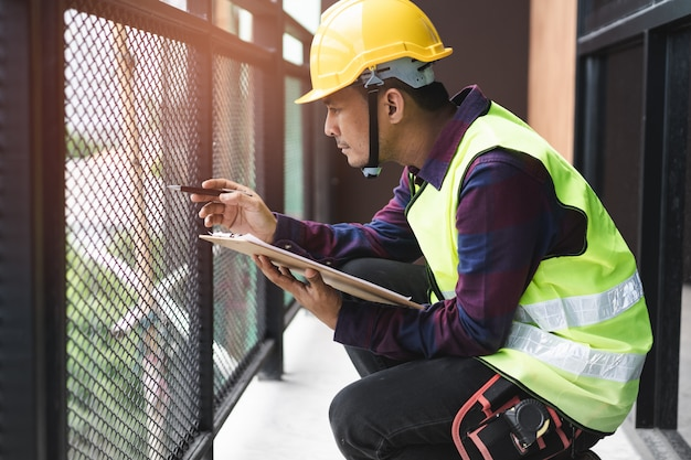 Hausinspektionsberatung. inspektor, der material des balkons überprüft und nach bruch sucht. Premium Fotos