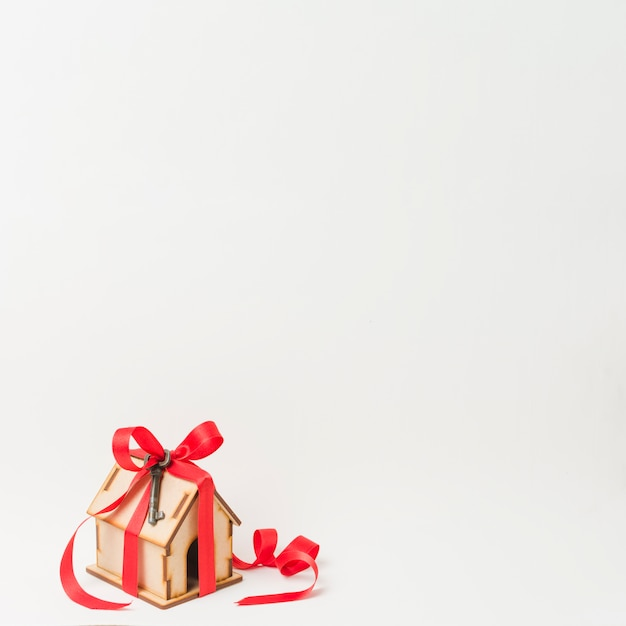 Hausmodell und metallischer schlüssel gebunden durch rotes band mit platz für text Kostenlose Fotos