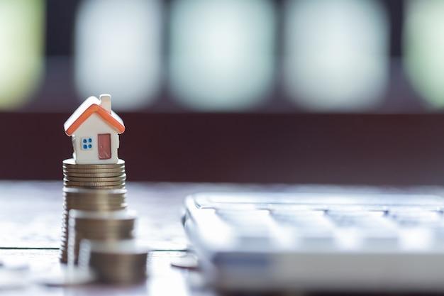 Hausmodell- und -münzenstapel mit taschenrechner als hintergrund. konzept für immobilienleiter. Premium Fotos