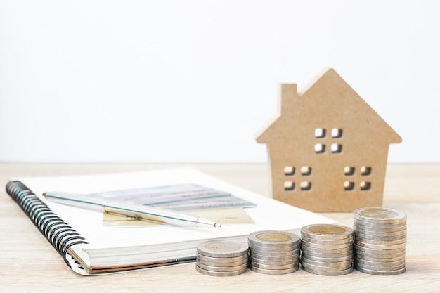 Hausmodell und notizblock mit münzen auf dem tisch Premium Fotos