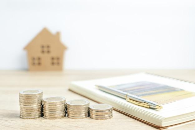 Hausmodell und notizblock mit münzen auf tisch für finanz- und bankkonzept Premium Fotos