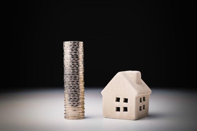 Hausmodell und reihe des münzengeldes auf weißer tabelle Premium Fotos