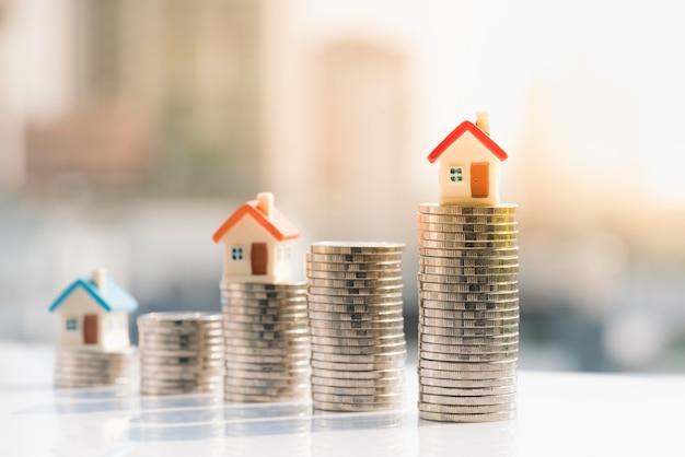 Hausmodelle auf münzenstapel mit stadthintergründen. Premium Fotos