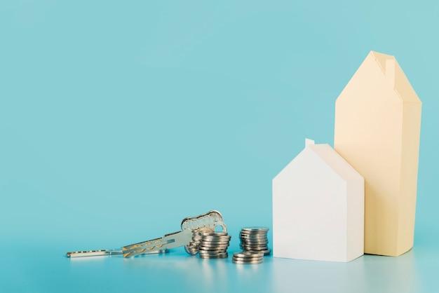 Hausschlüssel; stapel von münzen in der nähe der papierhäuser vor blauem hintergrund Kostenlose Fotos