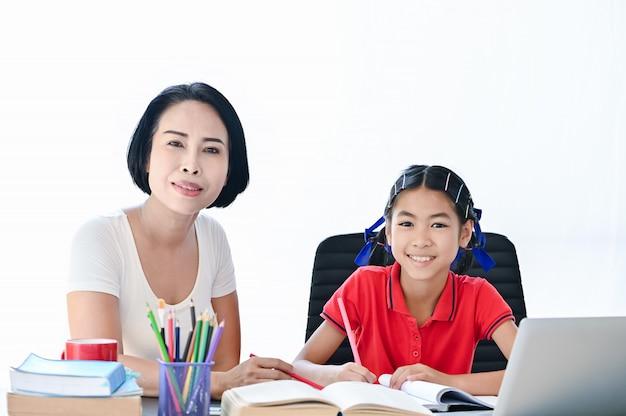 Hausschulkonzept, asiatische kinder und mutter lehren, hausarbeit der schule zu tun, die lächeln sieht Premium Fotos