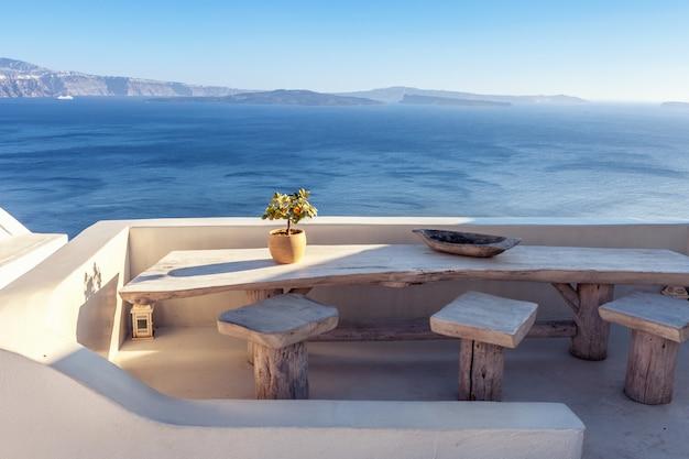Hausterrasse im freien mit hölzerner weinlesetabelle mit seeansicht in santorini, griechenland. Premium Fotos