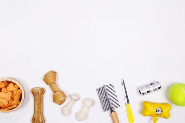 Haustierzubehör, -nahrung und -spielzeug auf weißem hintergrund. flach legen. draufsicht. Premium Fotos