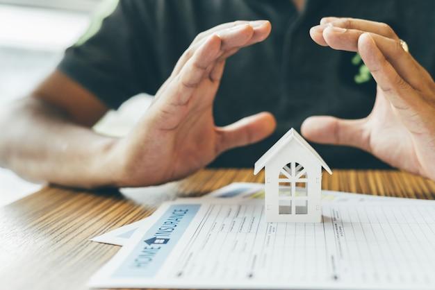 Hausversicherung oder objektschutz. versicherungsvertreter komplett, hölzernes musterhaus auf dem geld. Premium Fotos