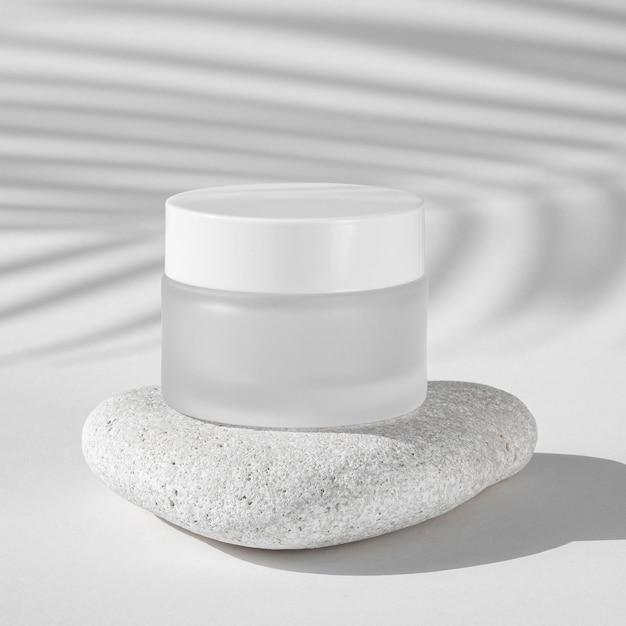 Hautpflege-feuchtigkeitsempfänger auf einem weißen felsen Kostenlose Fotos