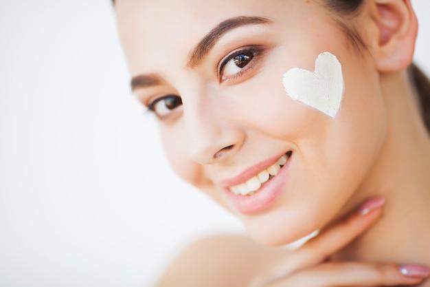 Hautpflege. schönes modell, das kosmetische cremebehandlung auf ihrem gesicht aufträgt Premium Fotos
