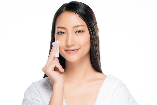 Hautpflegefrau, die gesichtsmake-up mit wattestäbchenauflage entfernt. Premium Fotos