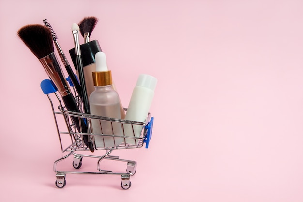 Hautpflegekosmetik und make-up-pinsel in einem lebensmitteleinkaufswagen auf rosa hintergrund Premium Fotos